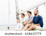 Small photo of Happy friends sitting together on a deck of a yacht and drinking an alcoholic drink.