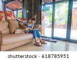 asia woman reading book on sofa ... | Shutterstock . vector #618785951
