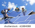 Workers installing alternative energy photovoltaic solar panels on roof - stock photo