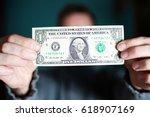 A Man Holds A U.s. 1 One Dollar.