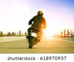 rear view of man riding... | Shutterstock . vector #618970937
