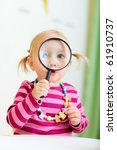 Adorable toddler girl looking through magnifier, perfect for early education context - stock photo