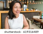 Small photo of Happy healthy Asian middle-aged business woman relaxing inside restaurant. Beautiful mature Chinese business woman portrait in fancy restaurant. Beauty aging skin care.