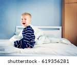 sleepy boy sitting in bed and... | Shutterstock . vector #619356281