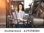 pretty woman filling her car... | Shutterstock . vector #619358084