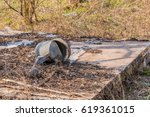Small photo of Old rusty watering can laying on makeshift table in a wooded area surrounded by tall grass in shrubs