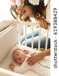 mother putting baby to sleep at ... | Shutterstock . vector #619388429