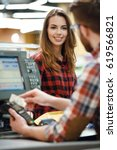 Small photo of Image of cashier man on workspace in supermarket shop create payment with credit card. Focus on lady near cashier's desk.