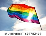 Small photo of Gay flag on sky background