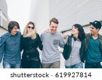 Stock photo group of multiethnic millenial friends walking arm around outdoor having fun togetherness 619927814