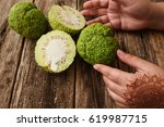 Small photo of Female hands with mehendi taking osage orange closeup. Asian woman with traditional decoration on hand holding green tropical Adam's apple fruit, old grungy wooden background