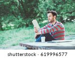 Young Man Reading A Book In Th...