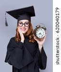 Small photo of photo of beautiful young alumnus with alarm clock on the wonderful grey studio background