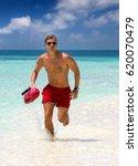 running lifeguard in tropical... | Shutterstock . vector #620070479