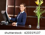Stock photo friendly concierge at hotel reception behind the counter 620319137