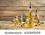 Small photo of Olive oil with spices on wooden background