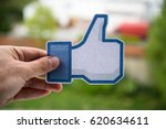 Small photo of Nitra, Slovakia, April 11, 2017: Man holding facebook like button printed on paper