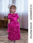 Small photo of Cute preschool girl dressed in pink dress and white bow acts in kindergarten