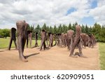 Small photo of POZNAN, POLAND - AUG 20, 2014: Iron 2 meter tall headless figures marching aimlessly across the Citadel Park in Poznan. The monument is called Unrecognised.