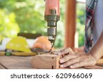 carpenter drills a hole with an ... | Shutterstock . vector #620966069
