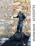 Small photo of LISBON, PORTUGAL - SEPTEMBER 25, 2014: Alive statue of warrior with pike entertaining people in the historic part of Lisbon