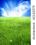 day summer or late spring meadow with cloudy sky and rays of light - stock photo