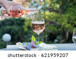 Stock photo waiter pouring a glass of cold rose wine outdoor terrace sunny day green garden background 621959207