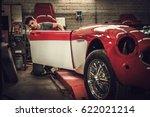 Mechanic working on car body details in restoration workshop - stock photo