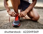 man tying running shoes | Shutterstock . vector #622049369