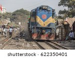 Small photo of Dhaka, Bangladesh - February 8, 2017: A train passing beside makeshift homes and people in a risky railway slum. Dhaka is one of the most densely populated cities in the world.