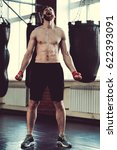 Small photo of Full length portrait of handsome bearded boxer with bare torso screaming in agony while training at the fight club