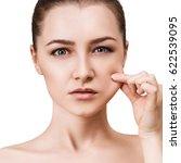 young woman pulls cheek's skin. | Shutterstock . vector #622539095