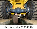repairman worker screwing nuts of axle assembly in heavy wheel loader - stock photo