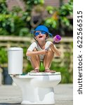 Small photo of Absurd picture: cute boy in goggles sitting on the toilet, which is installed in the middle of the street. Pan on his head