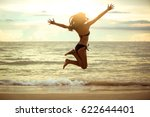 happy asian woman jumping on... | Shutterstock . vector #622644401