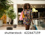 Small photo of Afro-american girl walking and smiling with a lot on shopping bags.