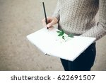 Close-up of hands holding notepad and pencil. Landscape designer / architect woman is planning new landscape project and drawing sketches and writing down notes and ideas - stock photo