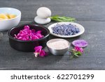 Small photo of pink linaria flowers and bath salt, dried lavender buds on black wood table