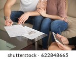 Small photo of Renting and tenancy concept. Close up of couple in love signing rental agreement sitting on couch with female realtor, starting living together, housing rent, residential property lease contract