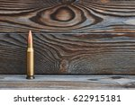 Small photo of Full metal jacket bullet on wooden background with copy space