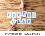 Small photo of Female hands and phrase EXPERT HELP on wooden background