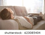 happy young man resting on sofa | Shutterstock . vector #623085404