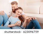 happy young couple sitting... | Shutterstock . vector #623096759