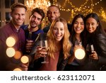 Small photo of Portrait Of Friends With Drinks Enjoying House Party