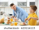 dad and son having lunch at home | Shutterstock . vector #623116115