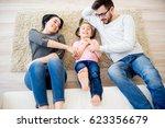 family lying on floor   Shutterstock . vector #623356679