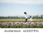 Small photo of Mother and daughter playing in a tulip field