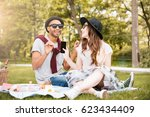 smiling young couple listening... | Shutterstock . vector #623434409