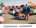 Small photo of FRANKFURT, GERMANY - AUGUST 23, 2015 : Pose of a confused old man looking at the camera and other people searching different objects in a haggle in Frankfurt.