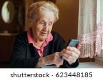 an old woman uses a smart phone. | Shutterstock . vector #623448185
